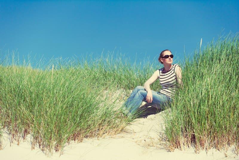 Giovane donna che si siede in dune di sabbia fra erba alta in Luskentyre, isola di Harris, Scozia fotografia stock