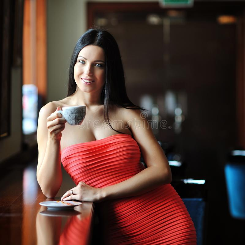 Giovane donna che si siede nel caffè con una tazza di caffè fotografia stock