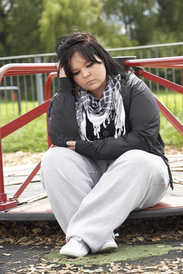 Giovane donna che si siede nel campo da giuoco fotografie stock