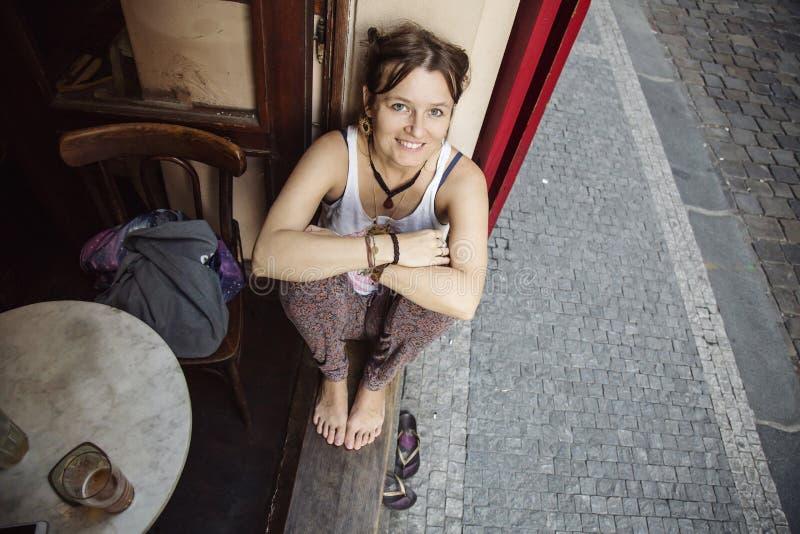 Giovane donna che si siede nella finestra del pub fotografia stock