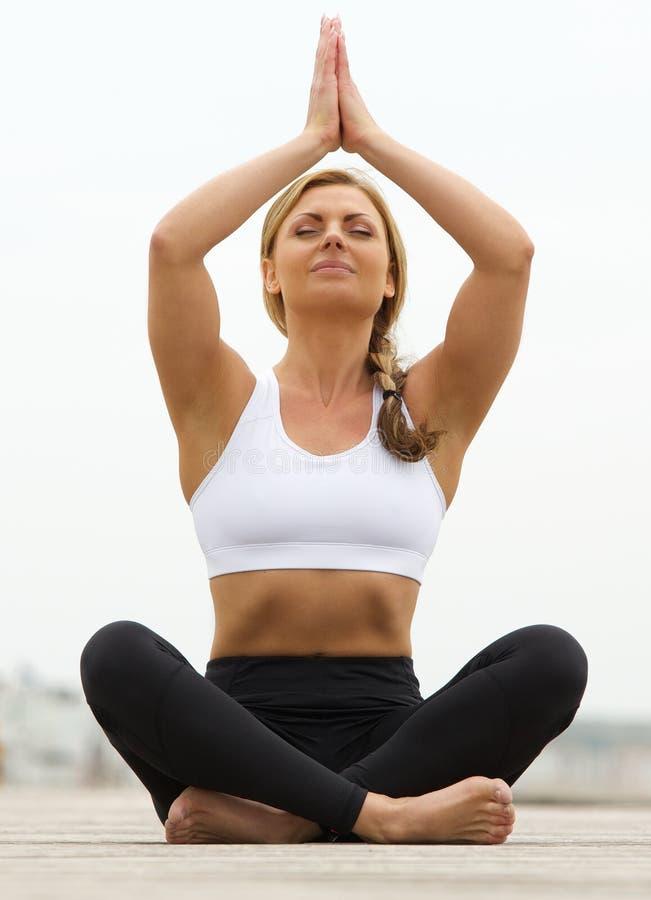 Giovane donna che si siede nella posa di yoga all'aperto fotografia stock