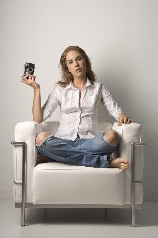 Giovane donna che si siede nella presidenza con la macchina fotografica fotografie stock