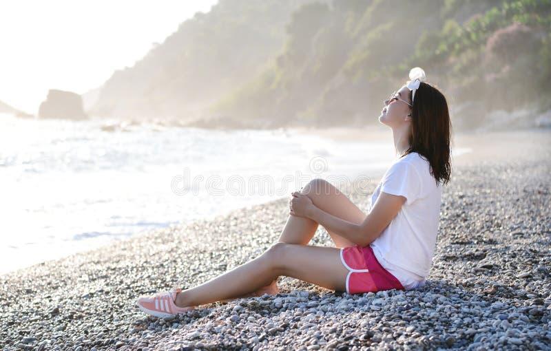 Giovane donna che si siede a Pebble Beach in mare il mar Mediterraneo fotografia stock