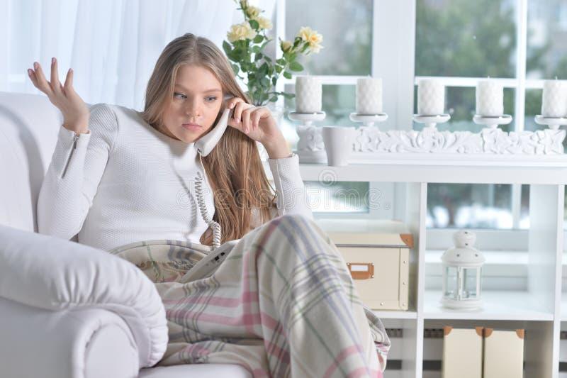 Giovane donna che si siede in poltrona e che parla sul telefono fotografia stock