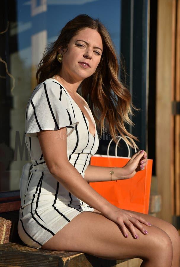 Giovane donna che si siede su un banco all'aperto immagini stock