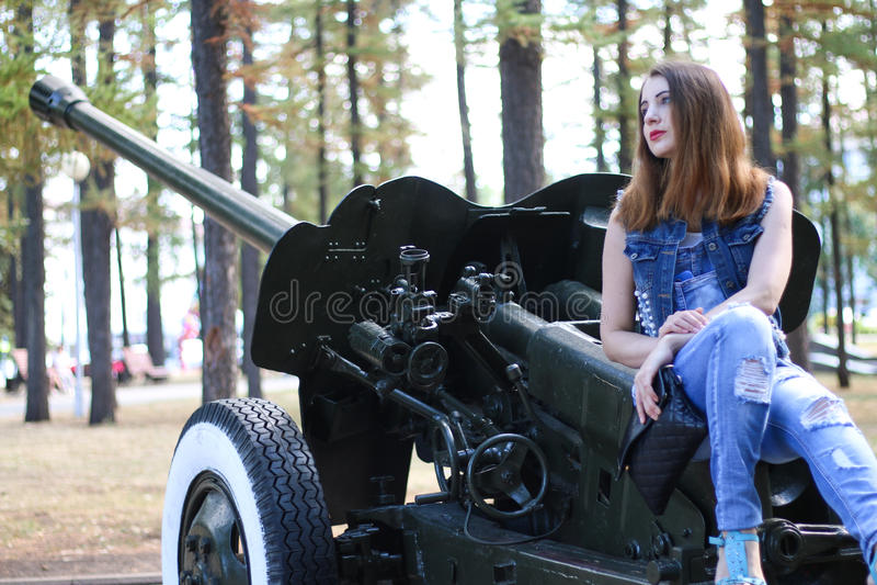 Giovane donna che si siede su un cannone dell'artiglieria fotografie stock libere da diritti