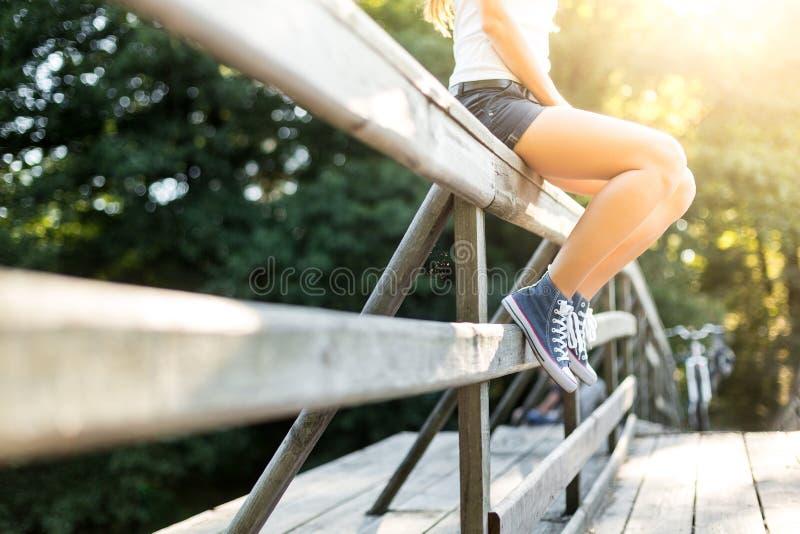 Giovane donna che si siede su un'inferriata del ponte in scarpe da tennis dei jeans fotografia stock libera da diritti