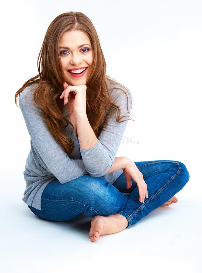 Giovane donna che si siede su un pavimento Isolato su priorità bassa bianca fotografie stock libere da diritti