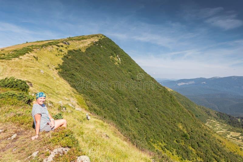 Giovane donna che si siede su una roccia fotografia stock