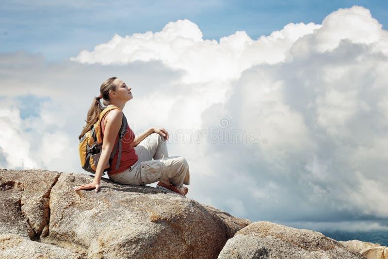 Giovane donna che si siede su una roccia con lo zaino. immagini stock
