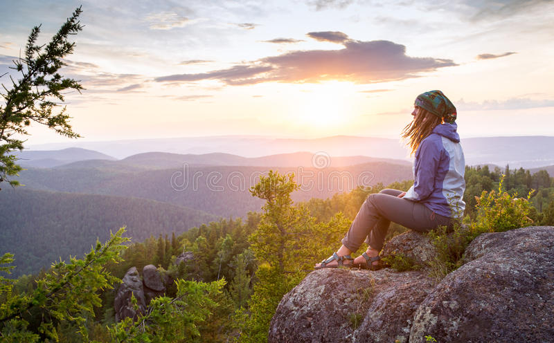 Giovane donna che si siede su una roccia, guardante al fotografia stock libera da diritti