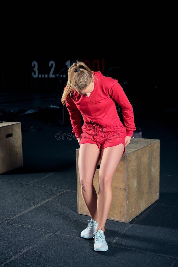 Giovane donna che si siede su una scatola alla palestra dopo il suo allenamento e che guarda giù immagini stock libere da diritti