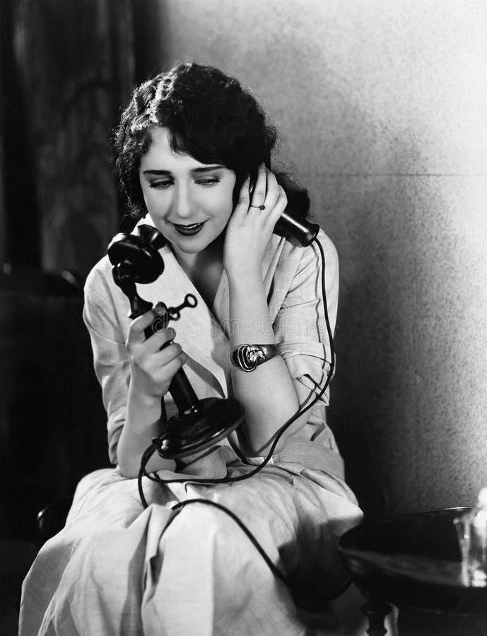 Giovane donna che si siede su una sedia che parla sul telefono (tutte le persone rappresentate non sono vivente più lungo e nessu fotografia stock