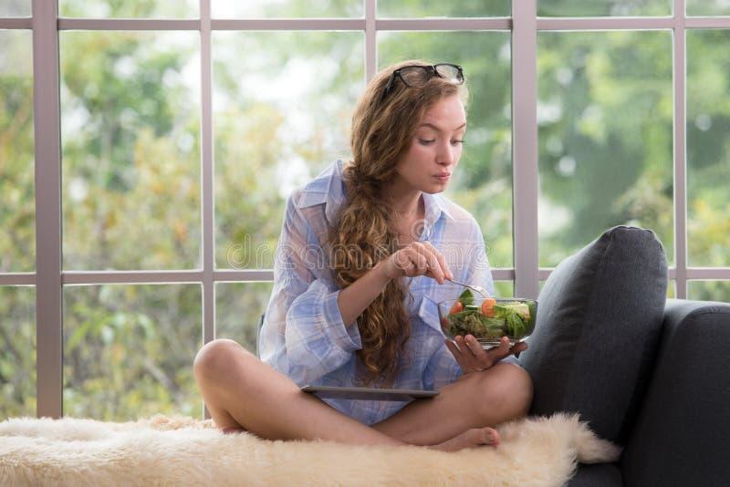 Giovane donna che si siede su uno strato facendo uso della compressa e che tiene un'insalatiera fotografia stock