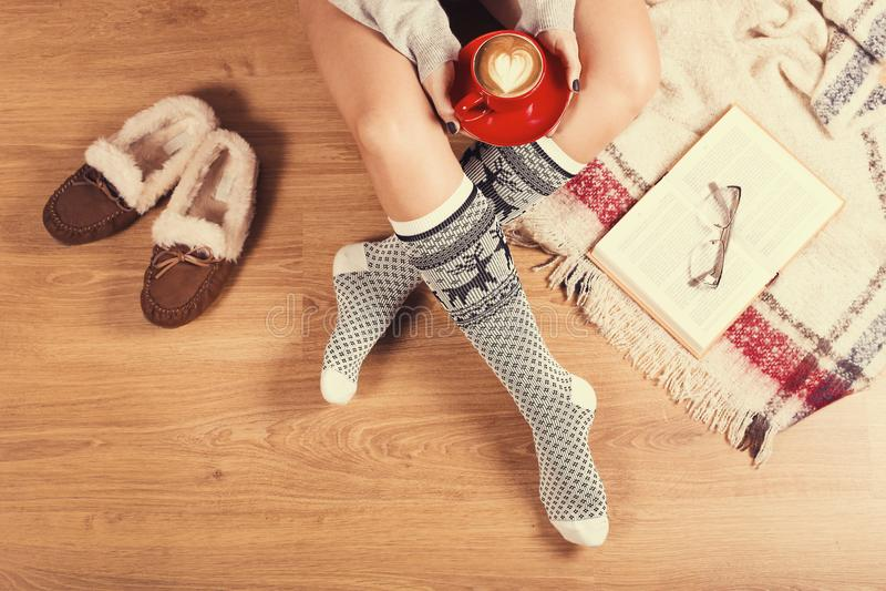 Giovane donna che si siede sul pavimento di legno con la tazza di caffè, il plaid, il biscotto ed il libro Primo piano delle gamb fotografia stock