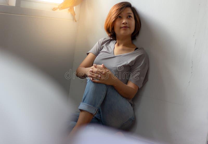 Giovane donna che si siede sul pavimento e che pensa a qualcosa al hom immagini stock