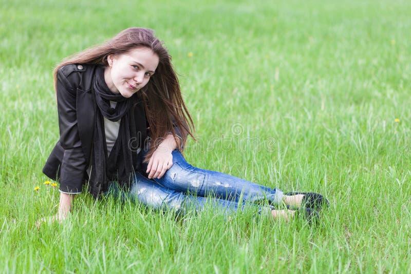 Giovane donna che si siede sul prato inglese fotografie stock