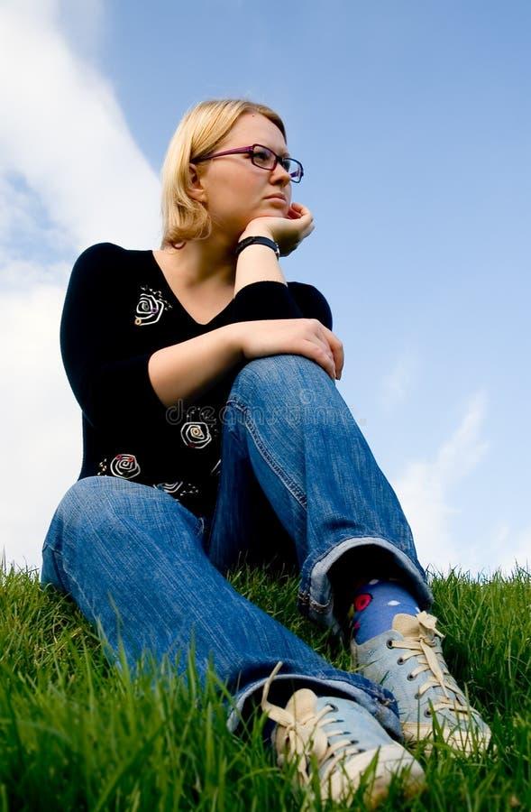 Giovane donna che si siede sull'erba fotografie stock