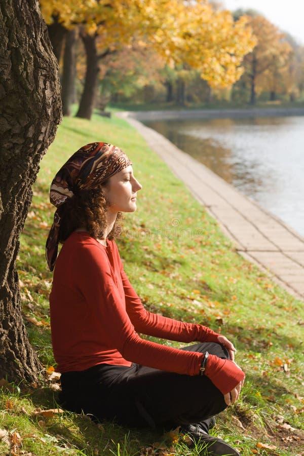 Giovane donna che si siede sull'erba verde fotografie stock