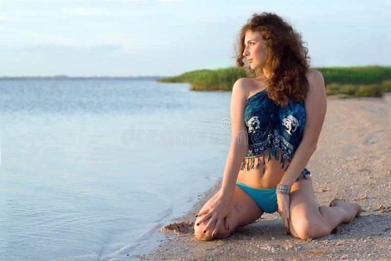 Giovane donna che si siede sulla baia immagine stock