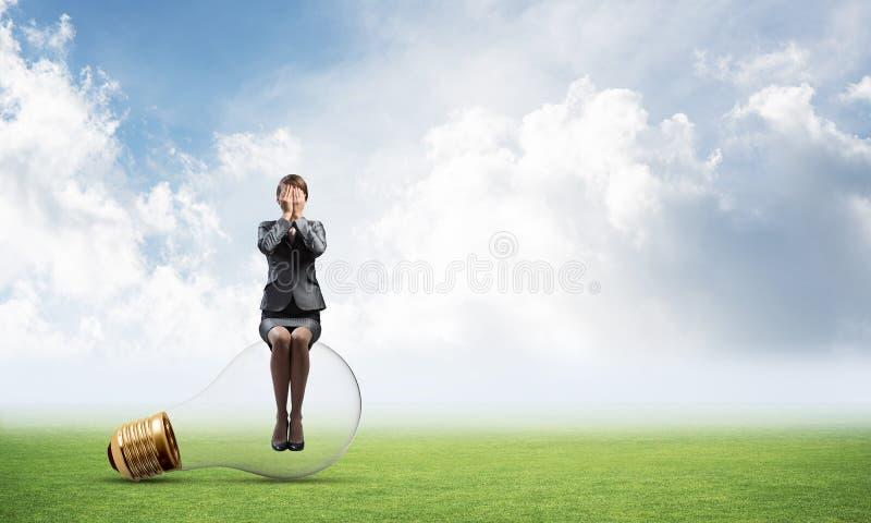 Giovane donna che si siede sulla grande lampadina immagini stock