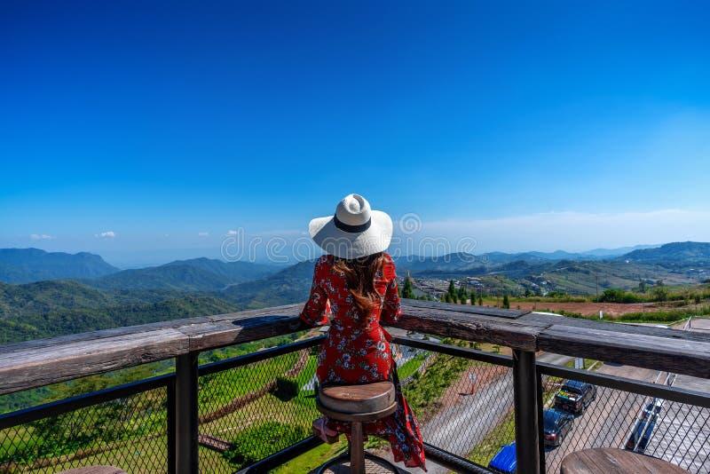 Giovane donna che si siede sulla piattaforma e che guarda al paesaggio della natura, Tailandia immagini stock libere da diritti