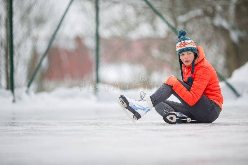 Giovane donna che si siede sulla pista di pattinaggio sul ghiaccio dopo la caduta immagine stock libera da diritti