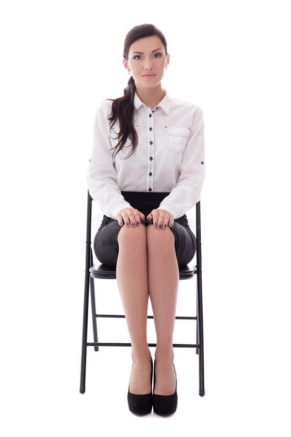 Giovane donna che si siede sulla sedia dell'ufficio isolata su bianco immagine stock libera da diritti