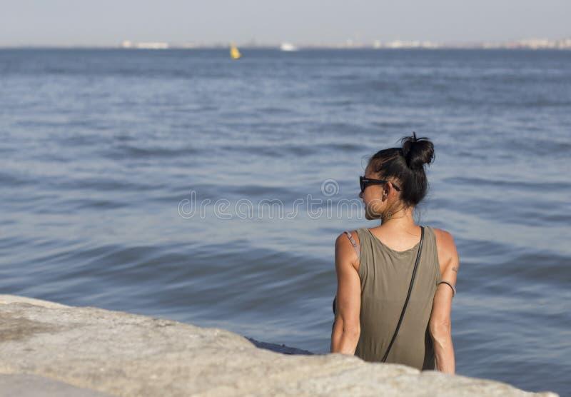 Giovane donna che si siede sulla spiaggia fotografie stock libere da diritti