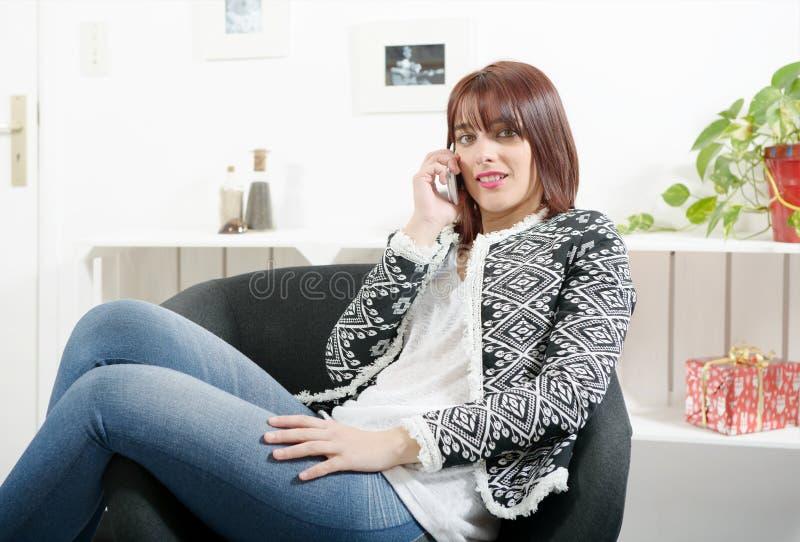 Giovane donna che si siede in una poltrona con un telefono immagini stock