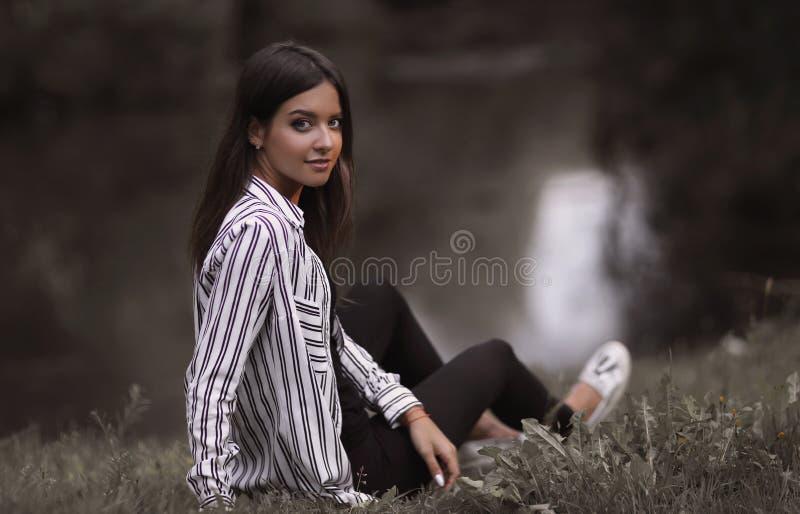 Giovane donna che si siede vicino al fiume fotografie stock libere da diritti