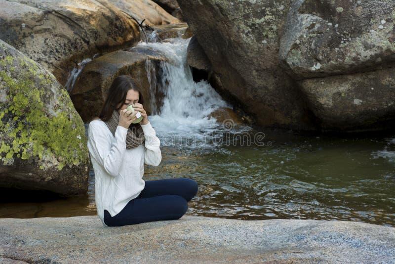Giovane donna che si siede vicino alla cascata ed al tè bevente, surroun fotografie stock libere da diritti