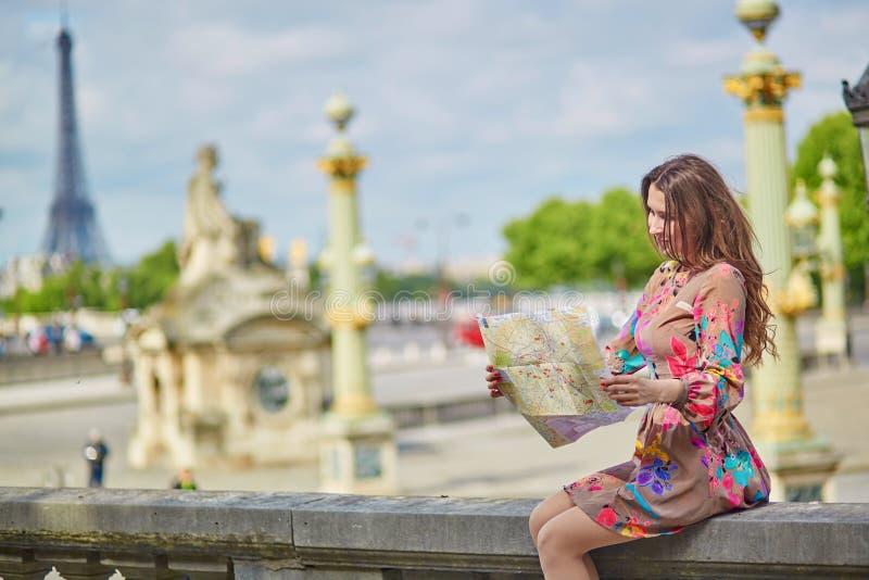 Giovane donna che si siede vicino alla torre Eiffel a Parigi fotografie stock libere da diritti