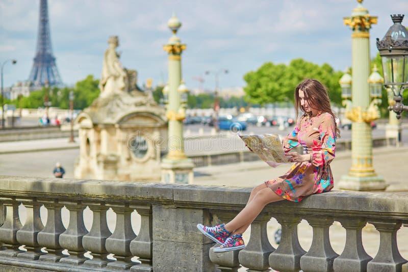 Giovane donna che si siede vicino alla torre Eiffel a Parigi immagini stock libere da diritti