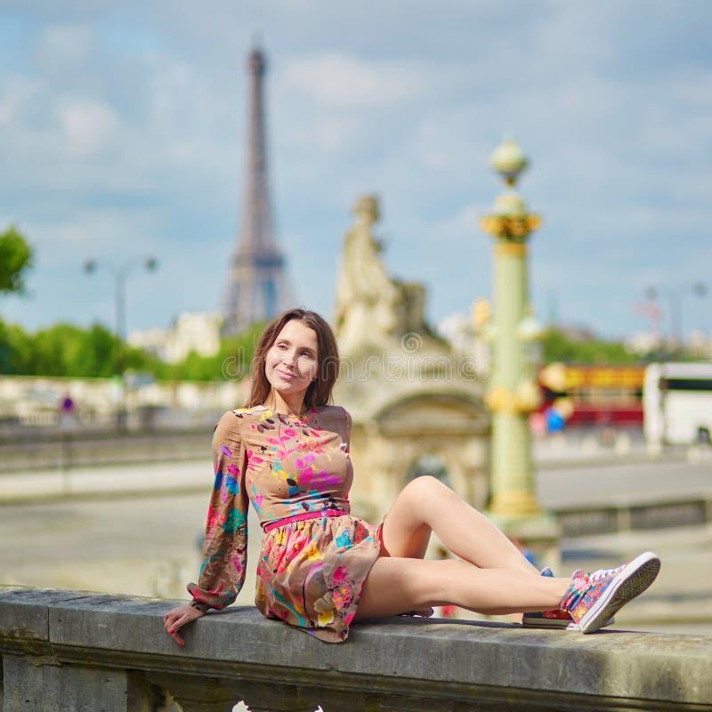 Giovane donna che si siede vicino alla torre Eiffel a Parigi fotografia stock libera da diritti