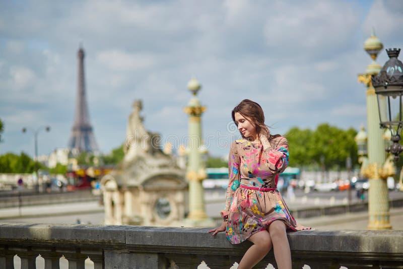 Giovane donna che si siede vicino alla torre Eiffel a Parigi immagine stock libera da diritti
