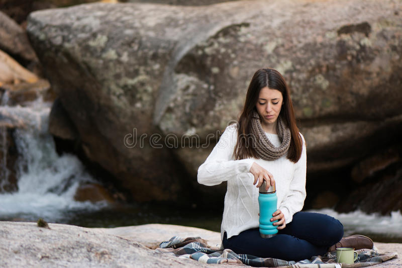 Giovane donna che si siedono vicino alla cascata, con un termos e maki fotografia stock libera da diritti