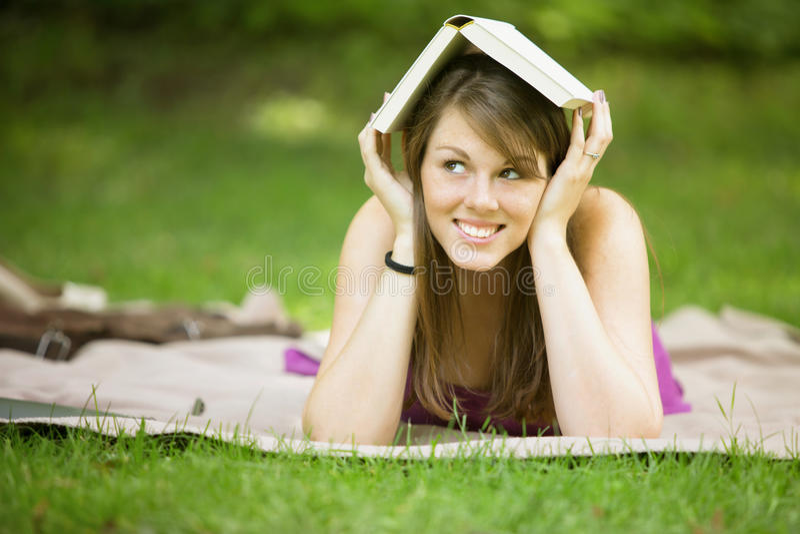 Giovane donna che si trova in libro della tenuta del parco sulla sua testa fotografia stock libera da diritti