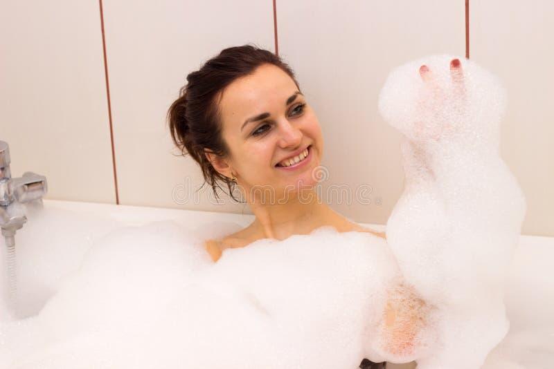 Giovane donna che si trova nel bagno immagine stock