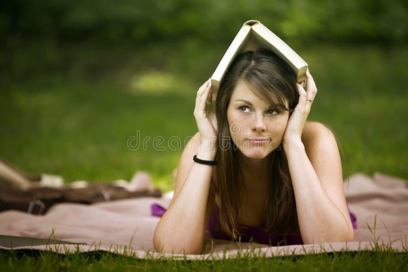 Giovane donna che si trova nel parco con il libro sulla sua testa immagini stock libere da diritti