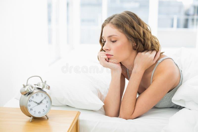 Giovane donna che si trova nel suo letto che esamina la sveglia fotografia stock libera da diritti