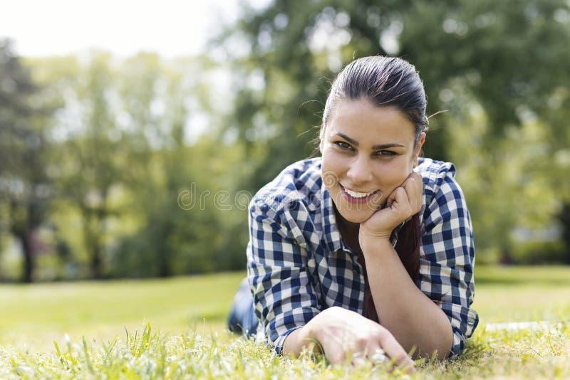 Giovane donna che si trova nell'erba al parco fotografia stock