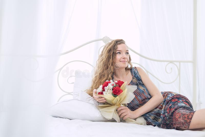 Giovane donna che si trova sul letto con il mazzo del fiore immagine stock