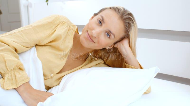 Giovane donna che si trova sul suo letto di mattina immagine stock