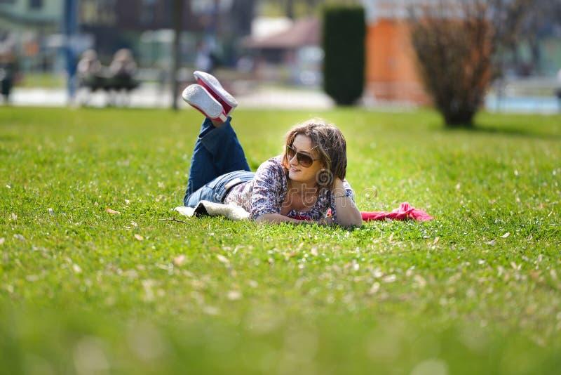 Giovane donna che si trova sull'erba di estate fotografia stock