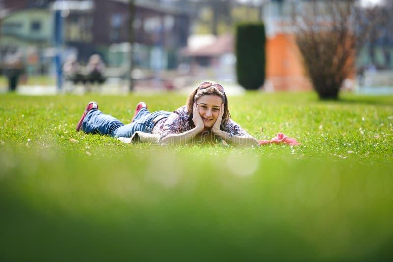 Giovane donna che si trova sull'erba di estate fotografia stock libera da diritti