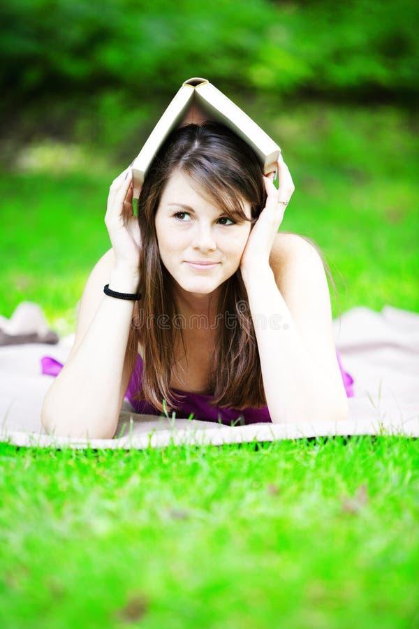 Giovane donna che si trova sulla coperta in parco con il libro sulla sua testa immagini stock