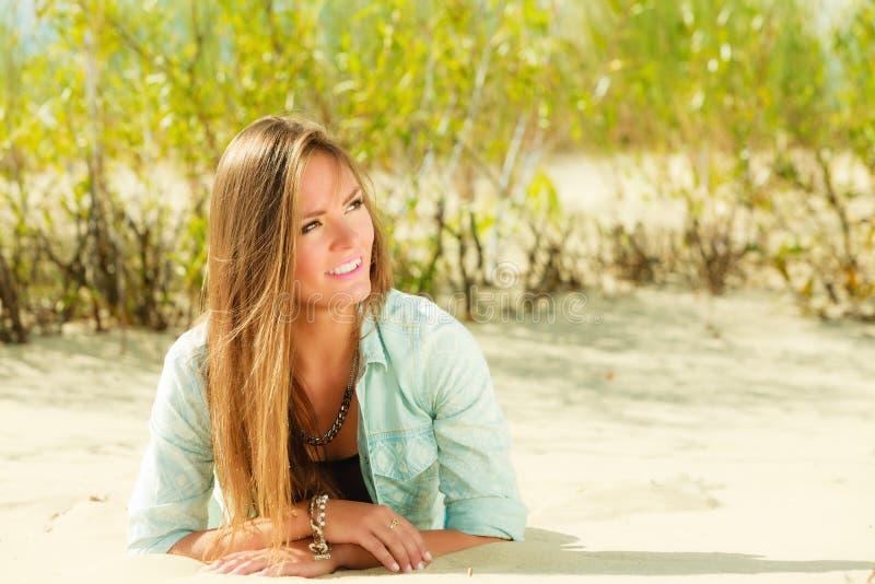 Giovane donna che si trova sulla duna erbosa immagine stock libera da diritti