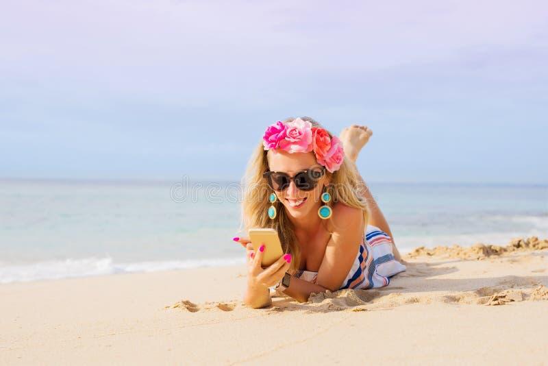 Giovane donna che si trova sulla spiaggia e che per mezzo del telefono cellulare immagine stock libera da diritti