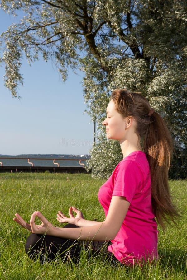 Giovane donna che siiting sull'erba nella posa di yoga immagini stock
